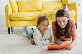 Happy Babysitter Lying On Carpet With Smiling Kid While Reading Book poster