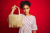 African american woman wearing fashion dress holding wicker bag over isolated red background with a  poster