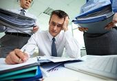 Perplexed accountant doing financial reports being surrounded by business partners with huge piles o