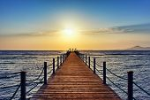 Bright And Colorful Sunrise Over The Sea And Pier. Perspective View Of A Wooden Pier On The Sea At S poster