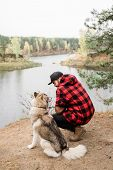 Young man in checkered jacket and black jeans sitting on squats by cute purebred pet while chilling  poster