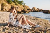 Image of beautiful hippy girl in feather headband sitting on sand by seaside in morning poster