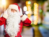 Middle age handsome man wearing Santa Claus costume and beard standing Trying to hear both hands on  poster
