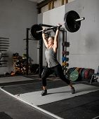 Strong femal weight lifter with heavy weights over her head, two thirds profile shot. poster