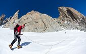 A male young climber walks along a glacier in the south face of Mont Blanc massif. Petit Capucin, Mont Blanc, France.