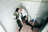 junger Mann ist betrunken sitzen auf Toilette, vermutlich ist er in einem club