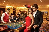 Beautiful Glamour Couple Against The Background Of Casino Poker Roulette. poster