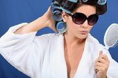 Woman with her hair in rollers holding a brush and wearing sunglasses