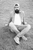 Opt For Simplicity Over Showiness. Fashion Man Sitting On Green Grass. Bearded Man In Fashion Denim  poster
