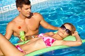 Romantic couple in outdoor pool at summertime.