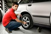 foto of auto repair shop  - A male changing a tire on a car - JPG