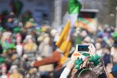 Hands Of Girl With Mobile Phone, Making Photo Of Carnival Of St. Patricks Day, Traditional Carnival  poster