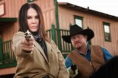 stock photo of hustler  - Pretty woman and partner aim guns in old west town - JPG