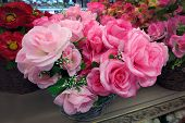 Artificial Pink Roses Close-up. In Baskets Are Bouquets Of Artificial Flowers For Sale. Artificial F poster