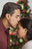 Hispanic man kissing wife on forehead