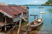 Thai Fishing Long Boat Next To The Fisherman Hut Standing On Stilts In The Water. Rusty Shack Roof.  poster