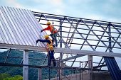Roofer Worker In Protective Uniform Wear And Gloves, Using Air Or Pneumatic Nail Gun And Installing  poster