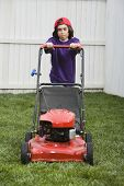 Mixed Race boy pushing lawn mower