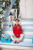 Merry Christmas, Happy Holidays! New Year. Little Girl In Sweater With Gift Sits On Porch Of House.  poster
