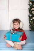 Merry Christmas, Happy Holidays! New Year 2020. Little Girl Sits In Red Sweater With A Gift On Porch poster