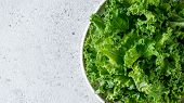 Kale Close Up. Green Vegetable Leaves, Top View In White Craft Bowl Over Gray Cement Background. Hea poster