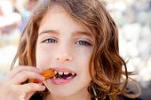 Blue eyes little girl eating churros fried crullers smiling