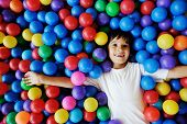 Happy children playing and having fun at kindergarten with colorful balls