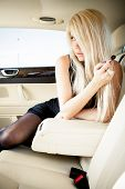 Young blond lady in sexy lingerie sitting on a backseat of a luxury car