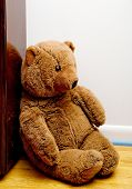 stock photo of stuffed animals  - A teddy bear sitting in a corner - JPG