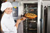 Portrait of beautiful chef placing pizza in oven at commercial kitchen