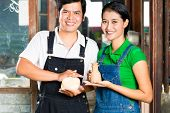 Two Asians or Indonesians holding proud baked clay and a finished handmade vase