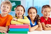 stock photo of diligent  - Group of diligent schoolchildren looking at camera in school - JPG