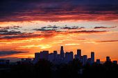 Fiery sunrise clouds over downtown Los Angeles city skyline.
