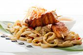 Udon (thick wheat noodles) with Skewered Salmon and Vegetables. Garnished with Banana Leaves and Sau