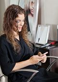 Young woman using mobile phone at beauty parlor