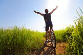 Young rider with bicycle standing in a green lush meadow with raised hands