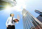 stock photo of winner man  - Young business man using laptop and look to blue sky and cloud with cityscape hong kong asia business and cloud computing concept - JPG