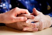 stock photo of compassion  - A young hand holding an elderly pair of hands - JPG