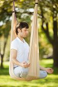 Anti-gravity Yoga, man doing yoga exercises in the park