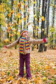 girl in autumn park toss leaves
