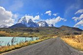 The gravel road along the shore of Lake Pehoe. The National Park Torres del Paine in Chile. In the distance are seen cliffs of Los Cuernos