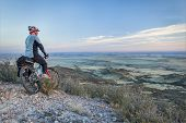 senior male on a mountain bike contemplating a view of rolling prairie at dusk, Soapstone Prairie Na