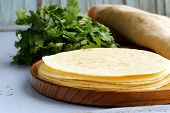 stack of corn tortillas on a wooden plate