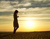 stock photo of thoughtfulness  - silhouette of a woman walking thoughtfully at sunset - JPG