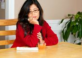 Asian woman in early forties sitting at table with drink, depressed