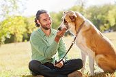 stock photo of shepherd dog  - Man and central Asian shepherd walk in the park - JPG
