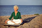 foto of rest-in-peace  - Elderly woman sitting on exercise mat doing meditation in lotus pose on the beach - JPG