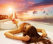stock photo of slim model  - Young sexy woman on her private yacht at sunset - JPG