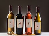 Four Wine Bottles with their labels spelling out the word SALE on a light to dark gray background. W