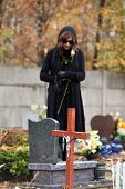 picture of headstones  - Woman in black standing above headstone holding white rose - JPG